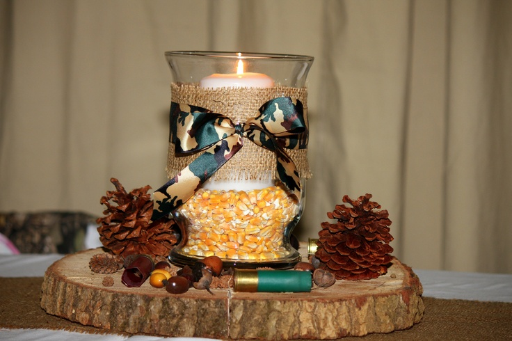 Our centerpieces were made out of tree slices, hurricane vases filled with corn and a candle, wrapped with burlap and a camo ribbon.  Pinecones, acorns and shotgun shell casings were also added