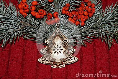 Christmas arrangement with gold christmas tree, red berries and  fir branches