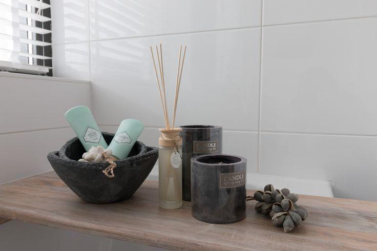 Sfeer in de badkamer met kaarsen, schelpjes, aardewerk en geurstokjes op een houten badplank. Styling @ Moods by Eef