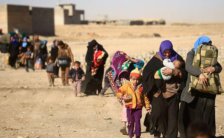 Pessoas deslocadas fugindo de militantes islâmicos no bairro de Tahrir, caminham em Mosul, Iraque