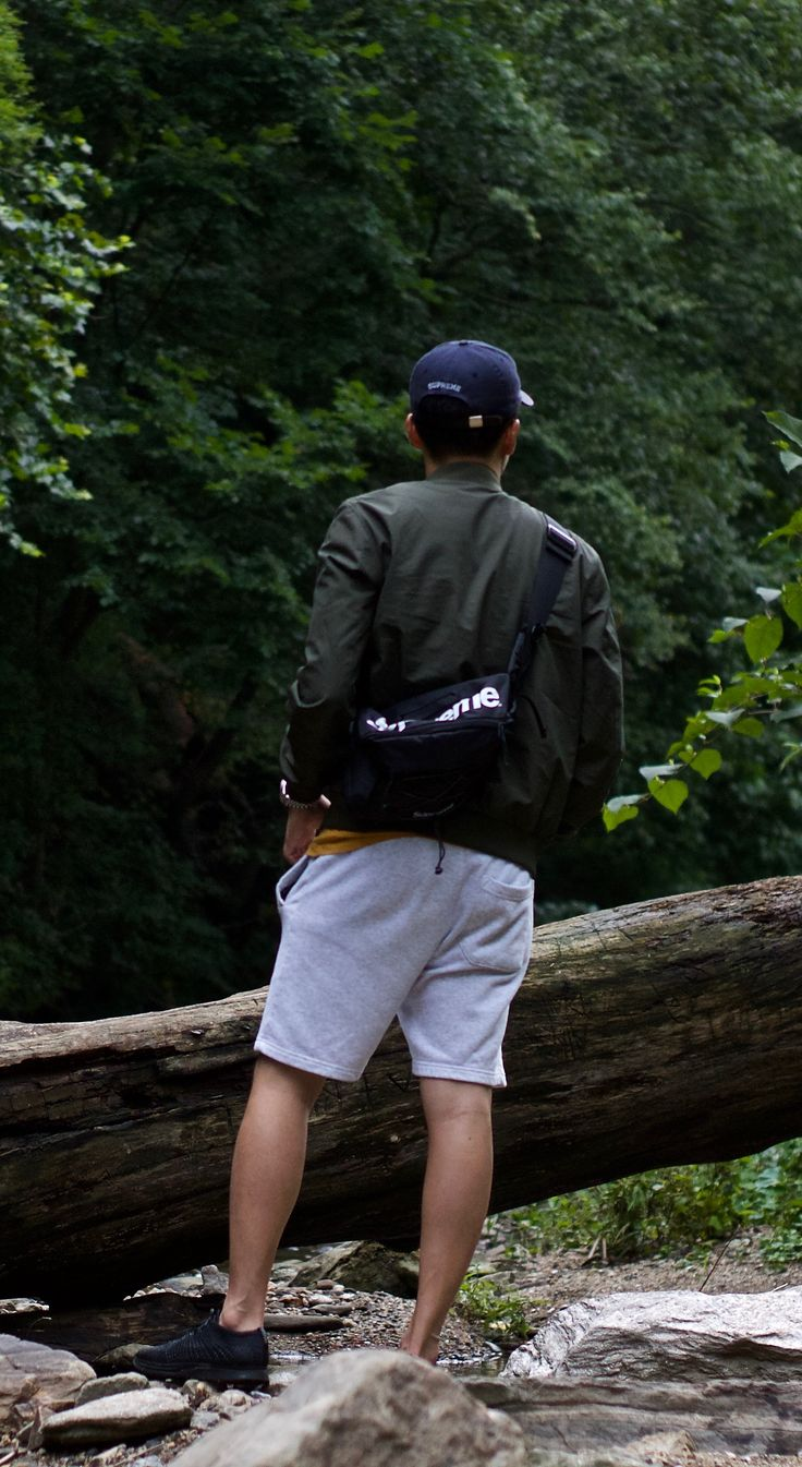 Perfect men's style hiking and outdoor look with some street style inspiration - Supreme shoulder bag and hat, Cos bomber jacket, Nike Fly Knit, and H&M shorts