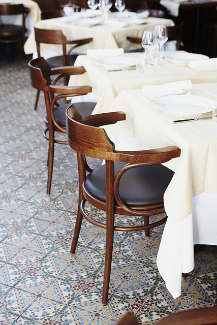 patterned floor . dark chairs . white linens & tableware