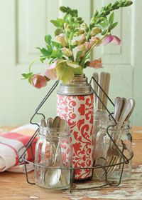 A vintage wire basket for canning jars for organizing silverware on a buffet table.