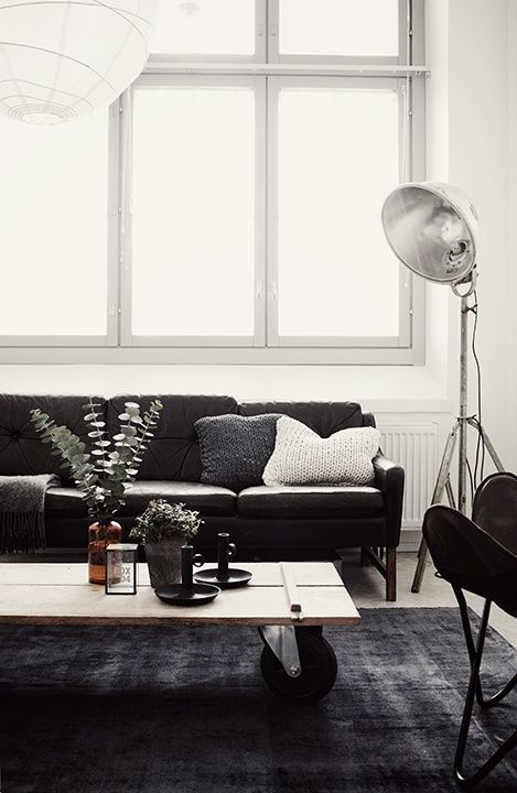 Living Room Via Netta-Natalia with the white walls combined with the dark sofa and carpet.