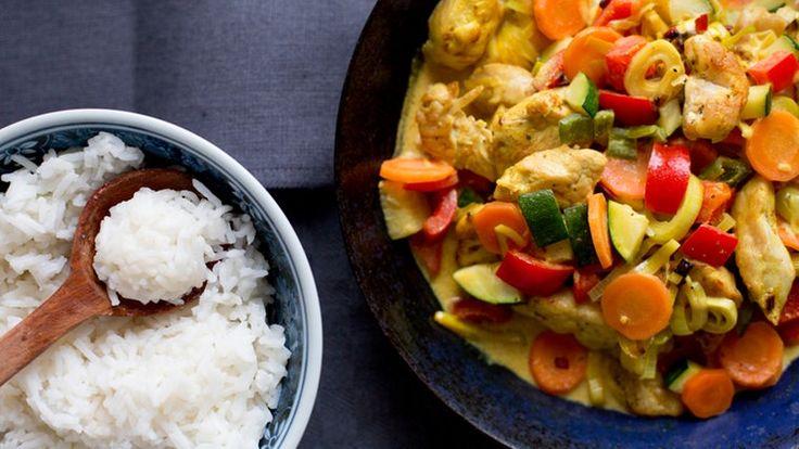 Gemüse-Putencurry in einer Pfanne und eine Schüssel mit Reis stehen auf dem Tisch.