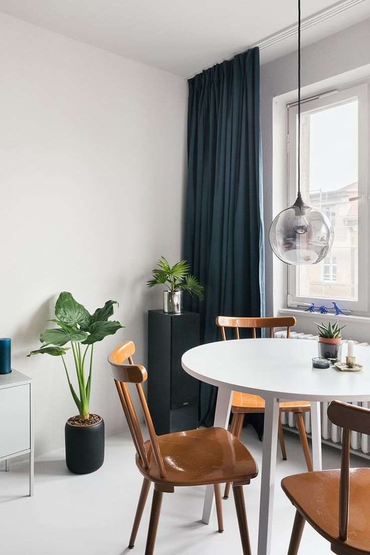 Monochrome dining area with some wooden vintage chairs, a round white table, a modern pendant light, green plants and dark blue curtains. We love this modern and minimal look! Check out the whole makeover on our website!