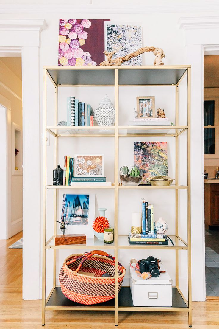 Gold painted bookshelf, white walls, colorful wall art and books, plants, and light wood floors