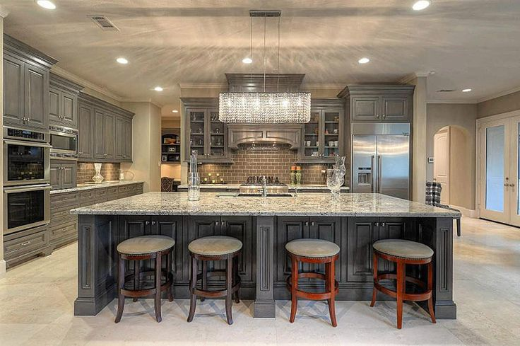 Custom wood island in luxury home with gunmetal color cabinets and chandelier