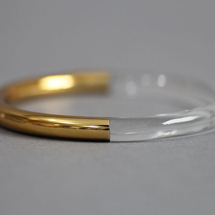「SIRI SIRI」とは「鎖」を意味するスワヒリ語「silisili 」にヒントを得た造語。ジュエリーには珍しい耐熱ガラスや籐、麻、天然木などを用いるなど 独自のスタイルを展開。耐熱ガラスにウレタン塗装を施した、異素材感溢れるモードなバングル。