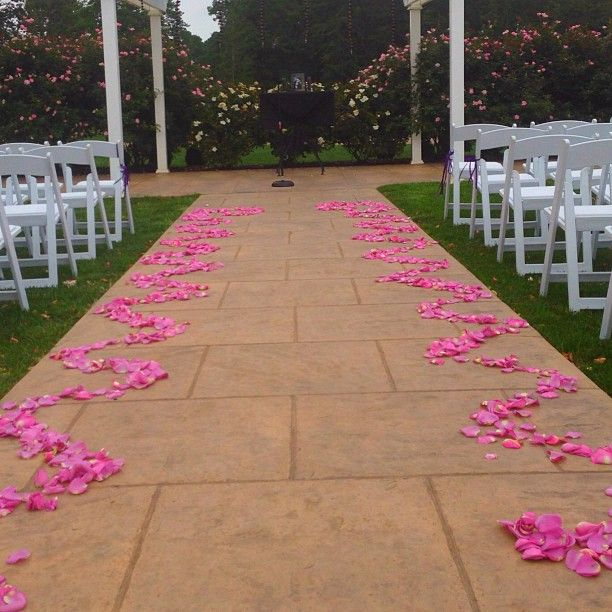 Pink rose petal design lines the aisle for a an outdoor ceremony at Running Deer Golf Club