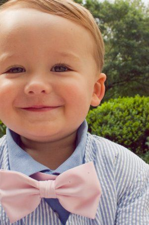 This lil gent is all dressed up in a pink bow tie and seersucker suit!