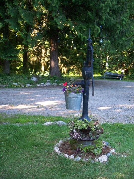We took an old water pump and placed it on a old insulator the placed a an old metal bucket of flowers on it.