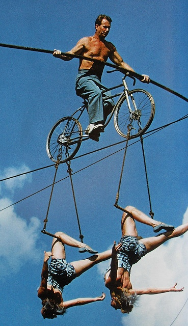 1950s Man Shirtless on highwire practice bicycle with two women circus performers
