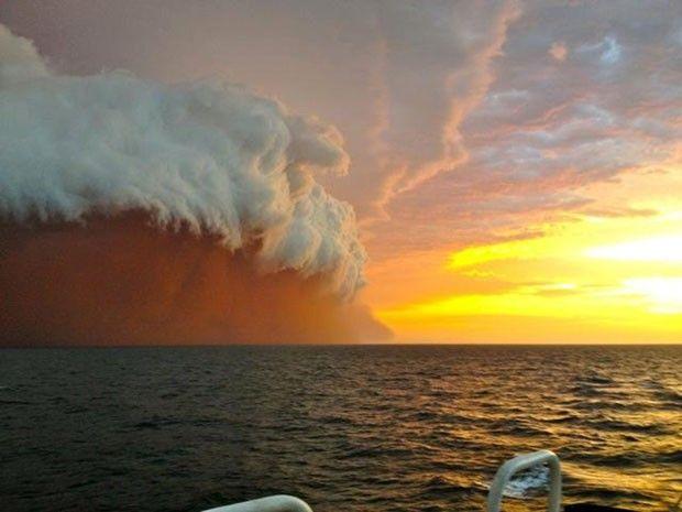 Fotos feitas de um navio rebocador na quinta-feira (09/01/2013) mostram a chegada de uma enorme nuvem de poeira vermelha na costa noroeste da Austrália.  Relatórios locais dizem que a tempestade de areia vermelha e pó foi trazida por ventos fortes no Oceano Índico e atingiram a cidade de Onslow
