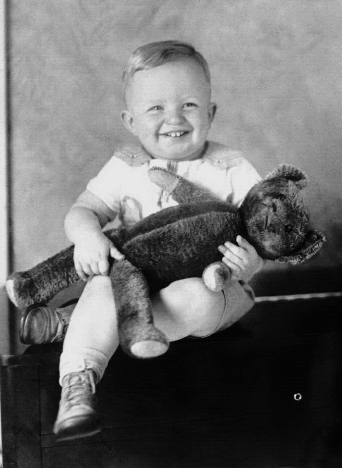 Vintage photo of smiling boy with his Teddy bear.