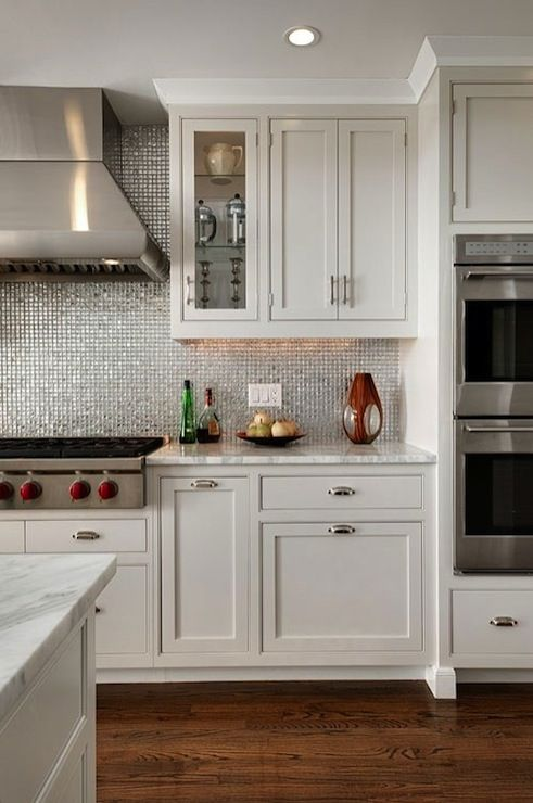 Modern, contemporary kitchen with white shaker kitchen cabinets, marble countertops, stainless steel tiles backsplash and double ovens.