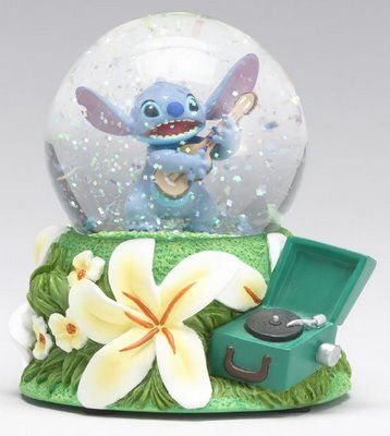 Disney Store Europe: Stitch Snowglobe. Sitch plays his guitar amongst the Hawaiian flowers.