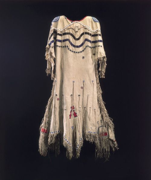 A NORTHERN PLAINS BEADED AND FRINGED WOMAN'S DRESS  BLACKFOOT   constructed of tanned hide, sinew sewn with glass beads in white, blue and black, faceted basket beads in blue and black, Russian trade beads translucent and blue, white porcelain beads, olivella shells, red, green and black wool, glass seed beads, red dyed porcupine quillwork and metal thimble, decorated with circle discs on shoulder and three rows of scalloped beadwork, fringe overall 58¼ x 65¼in.  Sold for $250,000.