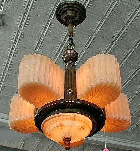 Original American Machine Age chandelier. Features five ribbed glass shades set in a brass plated fixture. Bottom shade provides downlight. A bakelite finial on bottom shade provides a multi-way switch to control multiple configurations of which lamps are turned on in which grouping.