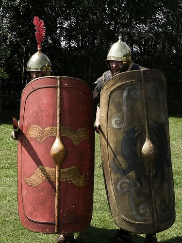 A regarder les films, on a parfois un peu l'impression que le bouclier romain est resté inchangé durant toute l'histoire romaine : rectangulaire en forme de tuile. C'est bien sûr inexact. La première armée romaine, fortement influencée par les Etrusques, est partagée en plusieurs classes censitaires. Autrement dit, à chaque niveau de fortune correspond un équipement différent.