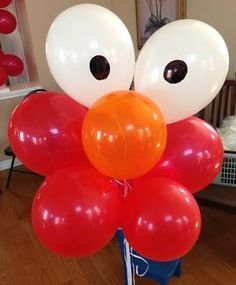 Elmo birthday balloon idea made with 4 red balloons, 2 white balloons & 1 orange balloon.  See more Elmo birthday party ideas at www.one-stop-party-ideas.com