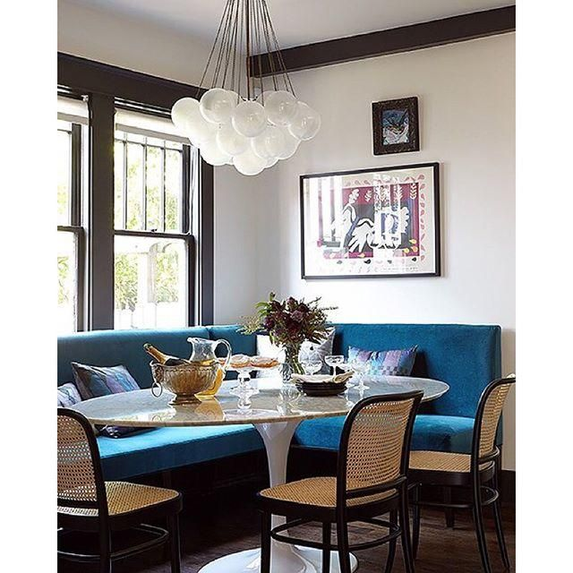 Gorgeous teal blue velvet breakfast nook with woven raffia dining chairs and a bubble cluster pendant chandelier light.