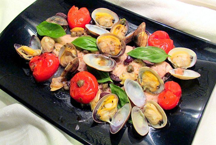 Filetto di Trota alla marinara Ingredienti per 2 persone: 200 g di vongole 2 filetti di trota di circa 250 g l'uno 10 pomodori Piccadilly 10 g di capperi dissalati 40 g di olive nere di Gaeta snocciolate 1 spicchio d'aglio 1 ciuffo di prezzemolo 1 peperoncino secco vino bianco secco 1 ciuffo di basilico 1 rametto di origano 3 cucchiai diolio extravergine di olivaGran Cru Per Liliana sale e pepe