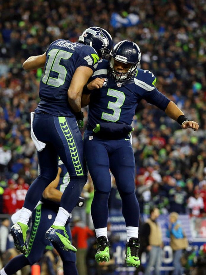 Wide receiver Jermaine Kearse #15 of the Seattle Seahawks celebrates with quarterback Russell Wilson #3 after Kearse catches a 35-yard touchdown against the San Francisco 49ers during the 2014 NFC Championship at CenturyLink Field in Seattle, Washington.