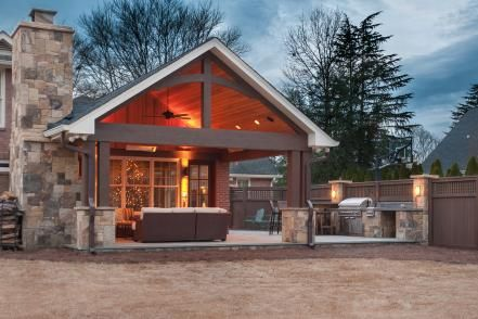 Craftsman-style abounds in this outdoor space with its exposed wood truss and vaulted ceiling, stone columns.