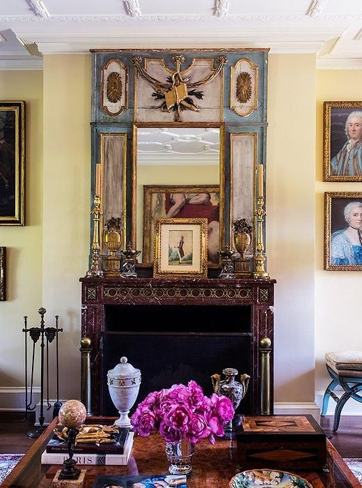 The walls are oatmeal-colored and the upholstery mostly neutral so as not to detract from the objects, including a striking red marble fireplace found in France.