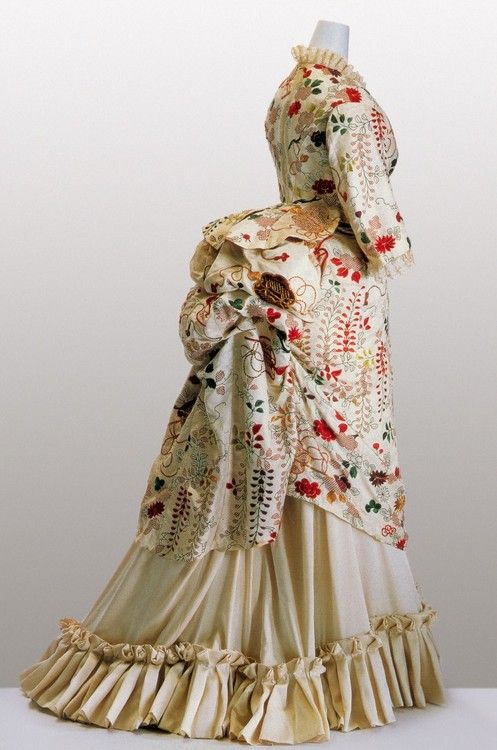 "1870's. KCI says: ""White kimono fabric of figured ""shibori"" silk satin; embroidery of wisteria, chrysanthemum, peony, and Chinese fan motifs in metallic threads ...This dress was remade from a Japanese kimono in London"""