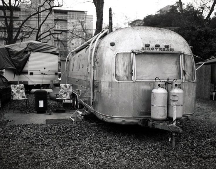 A photo of an old Airstream trailer in an RV park in Austin, Texas. Lived in and well used, this airstream is the embodiment of the American Dream, Non Stop Vacation in the open air! A great gift for