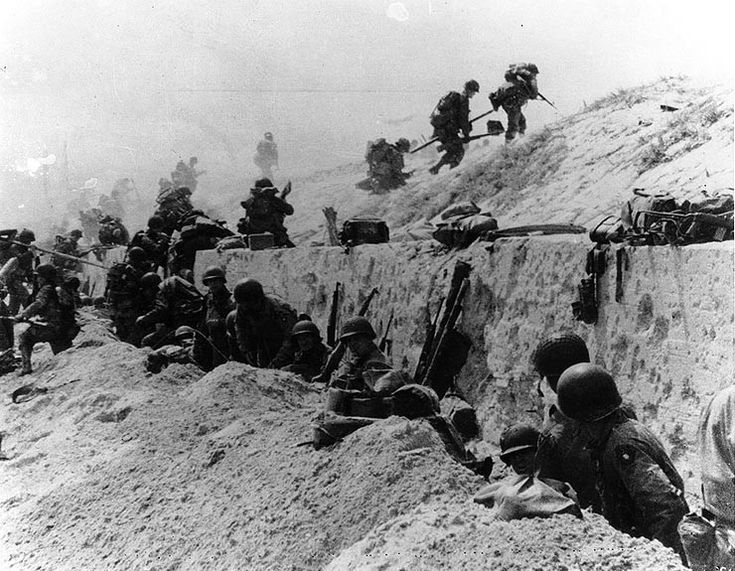 """U.S. Soldiers of the 8th Infantry Regiment, 4th Infantry Division, move out over the seawall on """"Utah"""" Beach, after coming ashore. Other troops are resting behind the concrete wall. Photo dated June 9, 1944, but probably taken on """"D-Day"""", June 6, 1944."""