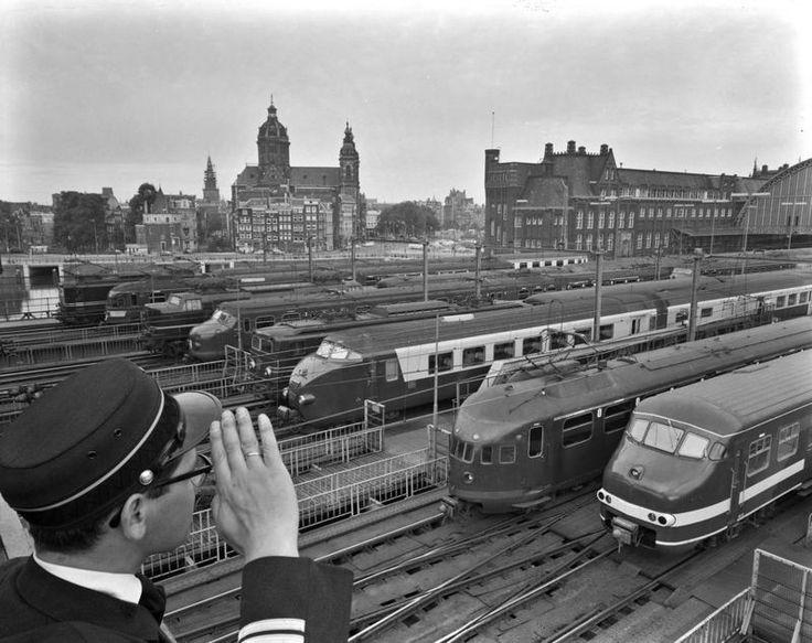 1964. A conductor of the Nederlandse Spoorwegen overlooks the marshalling yard…