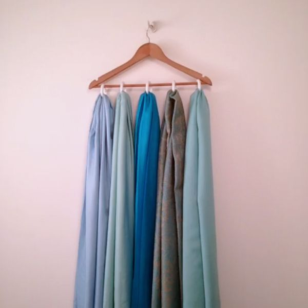 Easily organize scarves with shower curtain rings and a hanger.