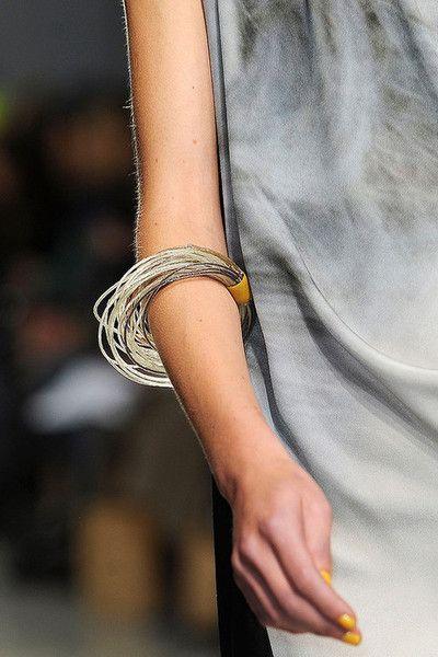 ..Las pulseras con un pequeño detalle amarillo , amarra con las manos , que reposan a los costados , de tonos grises