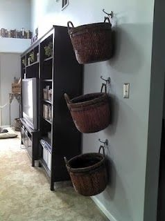 This is great, get pretty baskets and it adds to the decor and gets it up off the floor! Hang baskets on wall of family room for blankets, remotes, and general clutter. Inspired by ikea. Now THIS is a great idea.