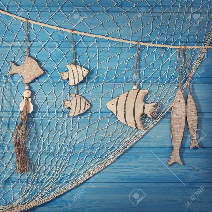 -marine-life-decoration-and-on-blue-shabby-background.  Blue-white-fishing-net-wall-bar-decoration-ceiling-dollarfish-hangings. decoración red pesca marina
