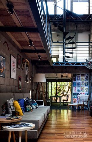 O andar de cima abriga o escritório. No estar, com piso de parquê, uma laje de concreto faz a base do sofá.