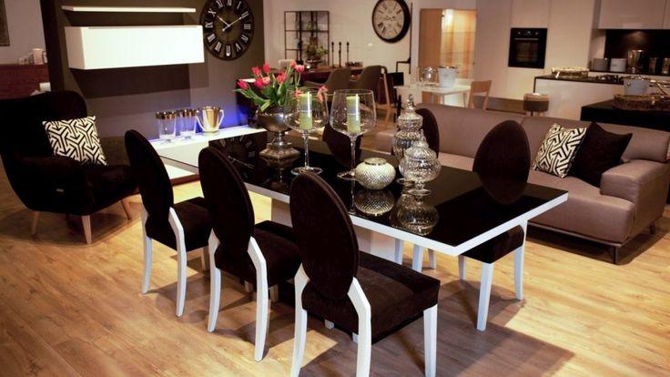 Nowoczesny stół i krzesła utrzymane w jednej linii stylistycznej. Prostokątny stół z blatem na wysoki połysk w kolorze czarnym i białym wykończeniu. Zamiast na 4 nogach, stół opiera się na solidnej podstawie. Stylizowane krzesła, tapicerowane miękkim materiałem w kolorze czarnym i kontrastujących białych nogach. To zestaw mebli do jadalni, który doda wnętrzu odrobiny stylu i szyku.