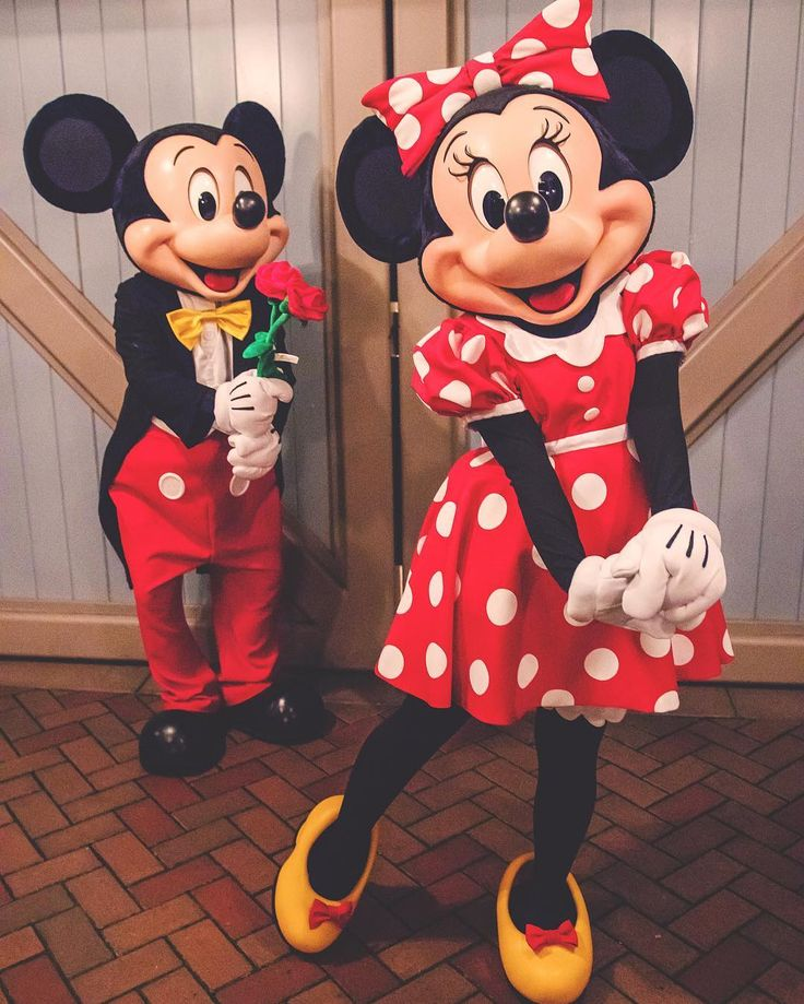 Minnie waiting to turn around and see a surprise from Mickey.