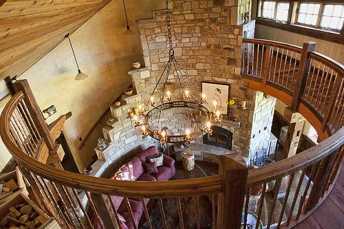 OMG, the curved staircase with that gorgeous fireplace- a wonderful use of space and a wonderful heat-sink. Castle-chic...