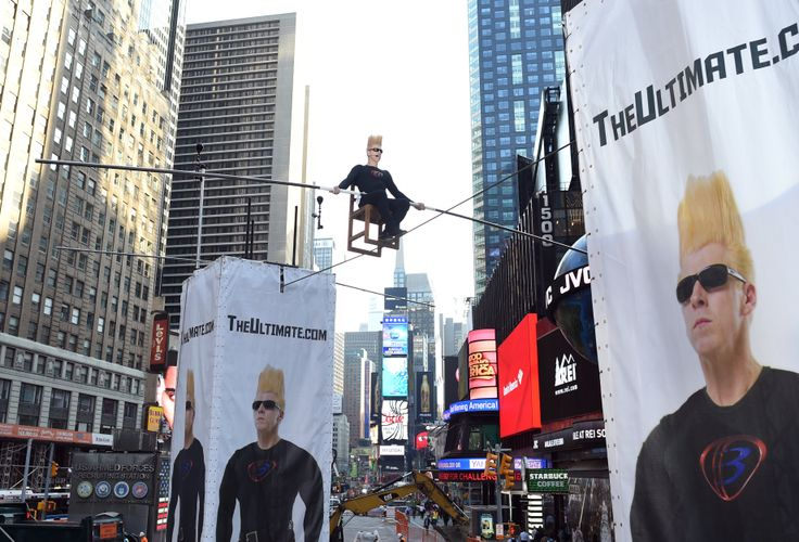 Bintang sirkus Bello Nock melintas dengan menggunakan kabel di atas Times Square di kota New York.