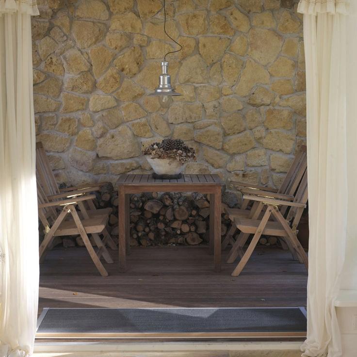 Intiem terras met mediterrane sfeer. Op dit overdekte terras zit je ook op regenachtige warme zomerdagen heerlijk buiten. De prachtige gele stenen die de wand bedekken, geven het terras een mediterrane sfeer. Bovendien heb je op dit terras een handige plek om het hout voor de open haard op te slaan. De deurmat is van RiZZ en heeft een teak-afwerking