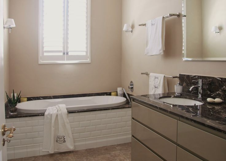 The white beveled Metro tile combined with the Marron Emperador marble and high gloss joinery work well in this space.