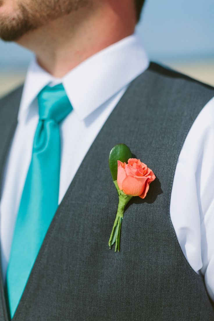 Groomsmen turquoise tie, charcoal vest, coral boutonnière. Beach wedding. Photo courtesy of Ashleigh Jayne Photography www.ashleighjayne.com