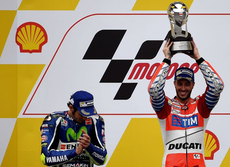 Second-placed Movistar Yamaha MotoGP's Italian rider Valentino Rossi (L) looks on as Ducati Team's Italian rider Andrea Dovizioso (R) holds up the winner's trophy as they celebrate on the podium after the 2016 Malaysian MotoGP at the Sepang International circuit on October 30, 2016. / AFP PHOTO / MANAN VATSYAYANA