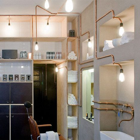 The copper tubes that branch across the walls and ceiling of this Amsterdam barber shop by Ard Hoksbergen carry both water and electricity (though not in the same pipes).