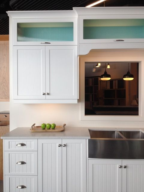 Beach-house inspired kitchen display features crisp white, beaded shaker doors with white interior on the majority of the kitchen.  Stunning upper glass cabinets bring this display alive with a vibrant blue custom finished interior.