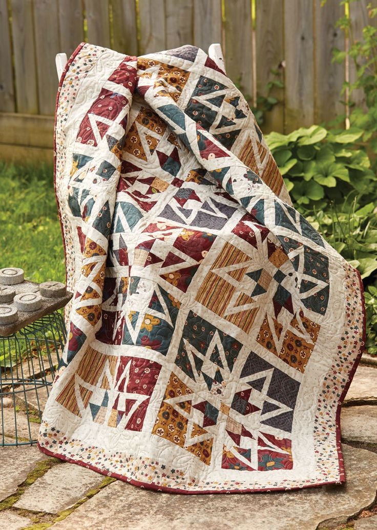 Highland Stars throw quilt pattern, by Wendy Sheppard, is the perfect quilt to challenge newer quilters and a wonderful project for seasoned quilters. These are no ordinary star blocks with light-colored strips diving each block. They're used to create contrast and outline the stars! A double border frames it all in!